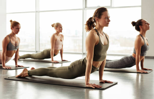 Group of sporty girls in sports bras keeping body on straight arms while doing cobra pose at yoga class stock photo