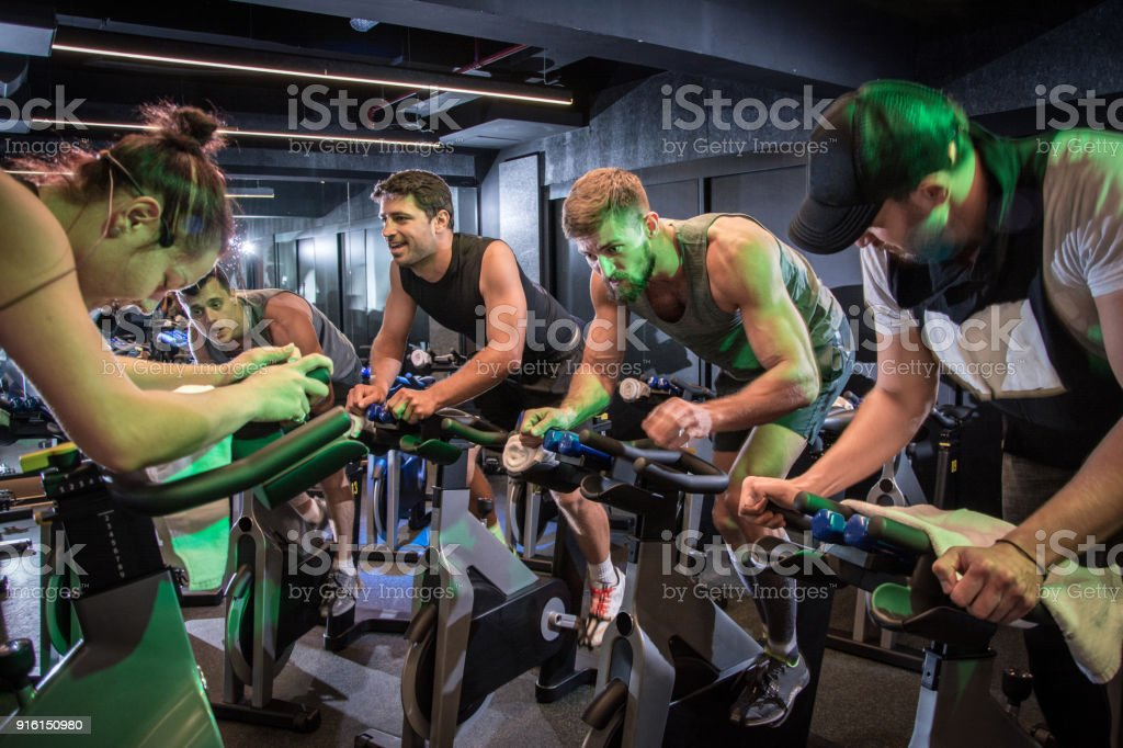 Group of sporty people cycling at gym. stock photo