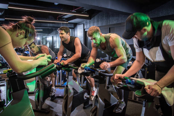 group of sporty people cycling at gym. - class стоковые фото и изображения