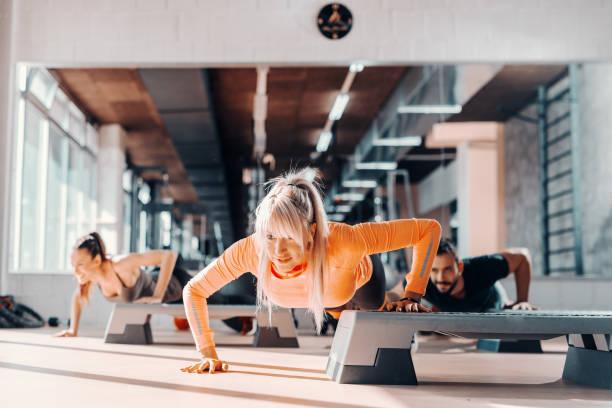 grupo deportivo haciendo push ups en steppers en gimnasio. enfoque selectivo en la mujer rubia, en espejo de fondo. - aeróbic fotografías e imágenes de stock