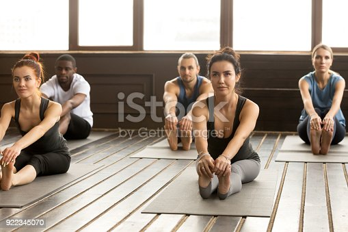 istock Group of sporty people in paschimottanasana exercise 922345070