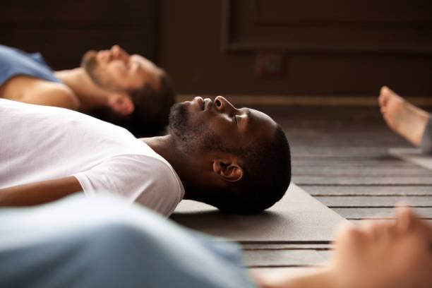 grup savasana'dan egzersiz sportif insan - yatmak stok fotoğraflar ve resimler