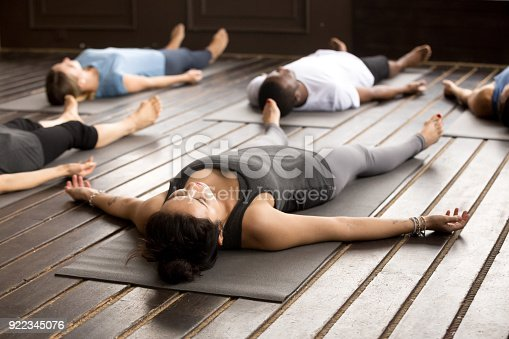 istock Group of sporty people in Savasana pose 922345076