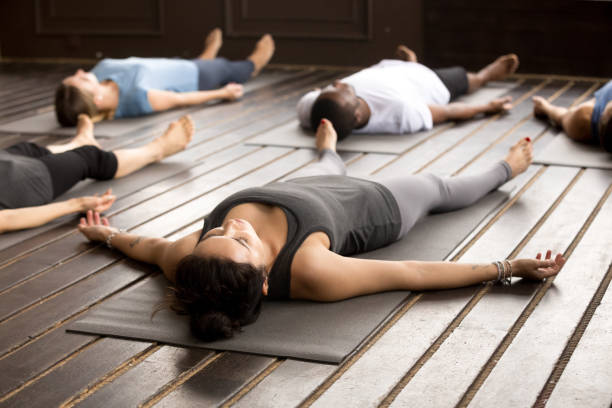 Group of sporty people in Savasana pose stock photo