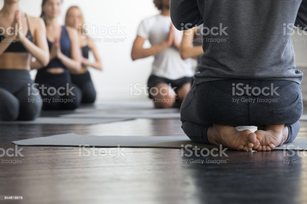 Group of sporty people in vajrasana exercise, close up stock photo