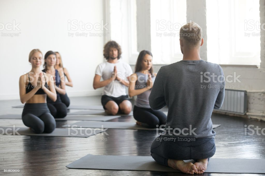 Group of sporty people in vajrasana exercise with instructor stock photo