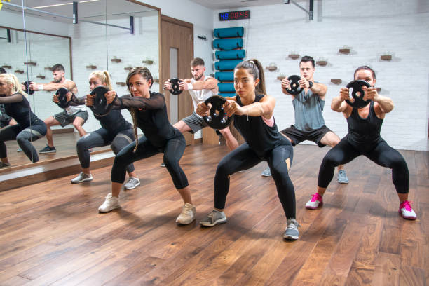group of sporty women and men exercising together with weight plates in health club. - class стоковые фото и изображения
