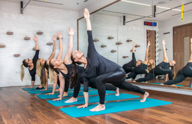 Group of sporty women exercising together in health club. Group of sporty women exercising together in health club. yoga class stock pictures, royalty-free photos & images