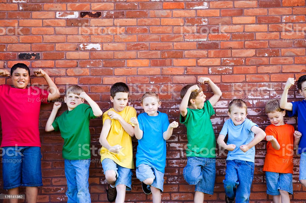 Group of Strong Young Boys Flexing by a Brick Wall stock photo