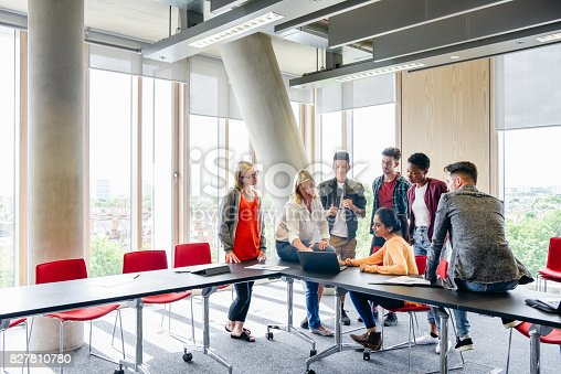 istock Group of students around table with laptop, teacher explaining 827810780