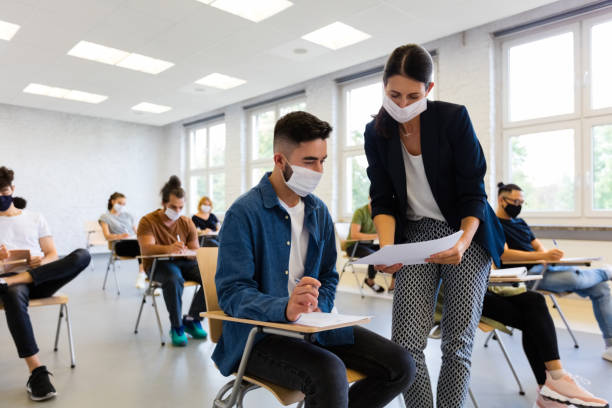 Group of students at lecture during coronavirus pandemic stock photo