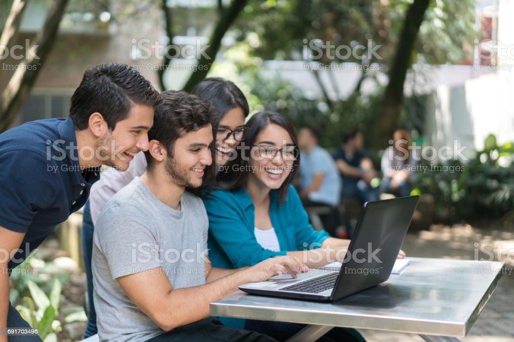 Gruppe von Studenten an der Universität mit einem Laptopcomputer – Foto