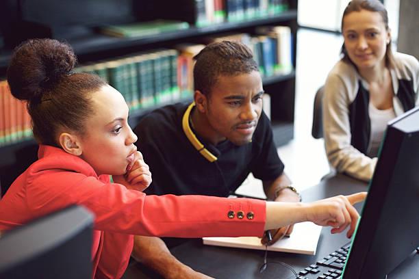 gruppe von studenten, die online recherche in der bibliothek - suche freundin stock-fotos und bilder