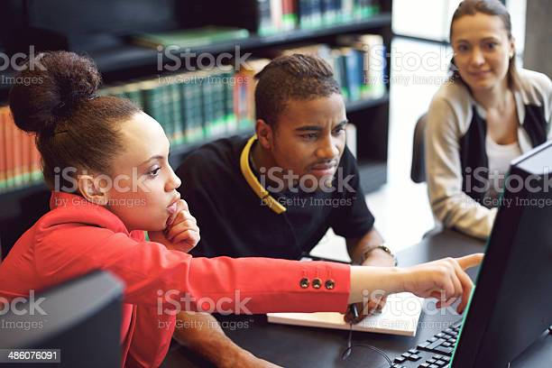 Group Of Students Doing Online Research In Library Stock Photo - Download Image Now