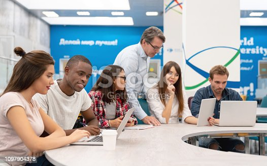 Group of students in an IT class talking to their teacher - education concepts