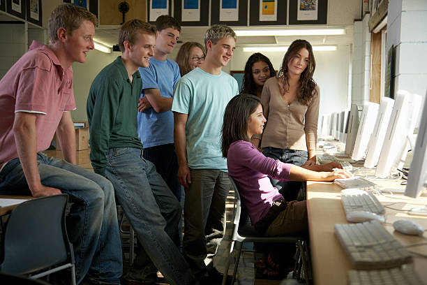 Group of students in computer room, looking at same screen stock photo