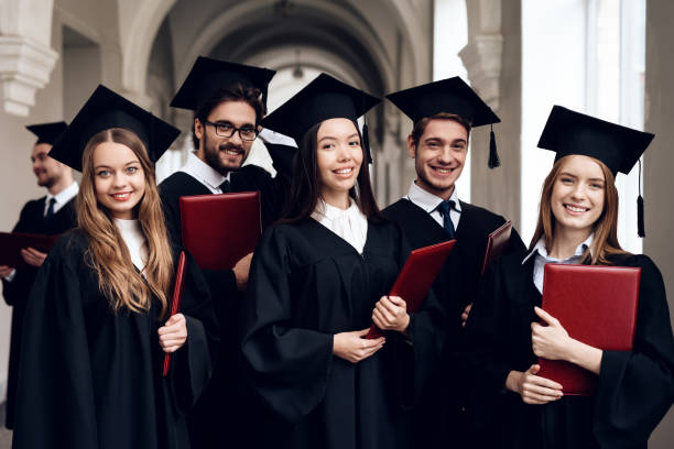 A group of students in mantles are standing in the corridor of the university. A group of students in mantles are standing in the corridor of the university. They are university graduates. They are very happy about this. alumnus stock pictures, royalty-free photos & images