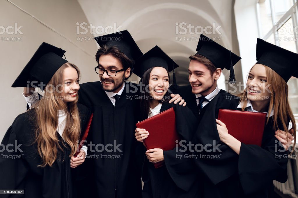 A group of students in mantles are standing in the corridor of the university. stock photo