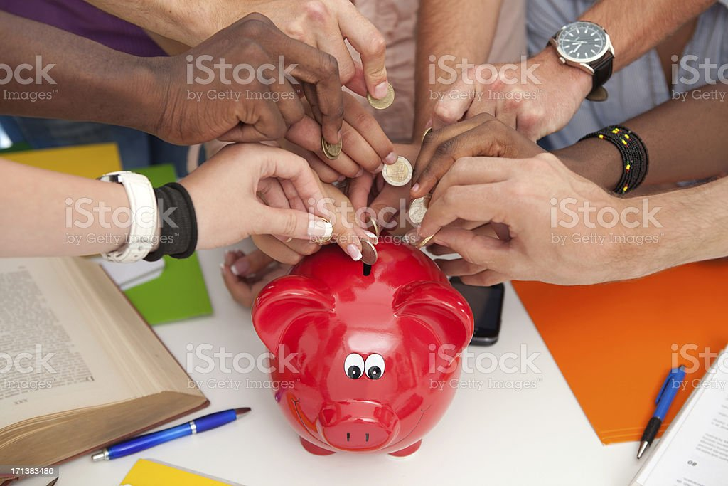 Group of students inserting coins to a piggy bank. royalty-free stock photo