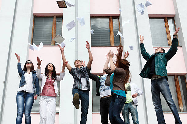 A group of students jump in the air stock photo