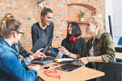 Group Of Students Learning Together Using Ebook Stock Photo - Download Image Now