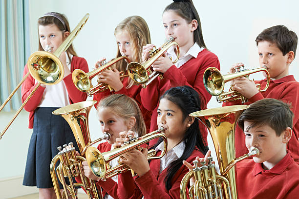group of students playing in school orchestra together - performance group stock photos and pictures