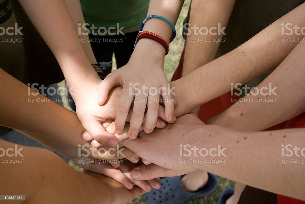 A group of students put their hands together as a team  stock photo