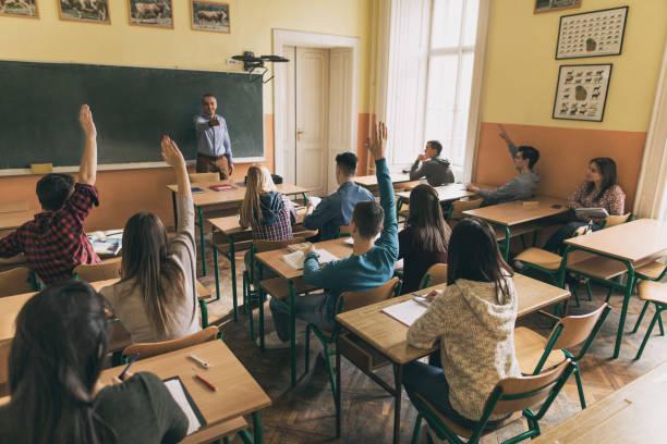 group of students raising hands to answer teacher's question in the classroom. - professore di scuola superiore foto e immagini stock