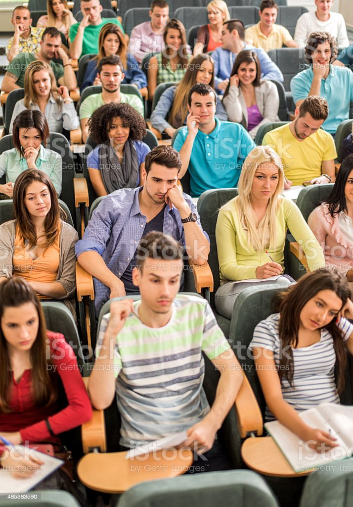 Group of students sitting in amphitheatre listening to a lecture. stock photo