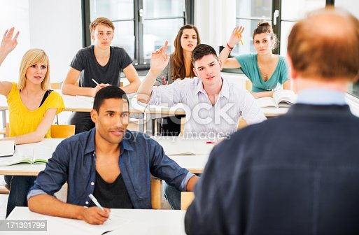 600055398 istock photo Group of students sitting in classroom with raised hands. 171301799