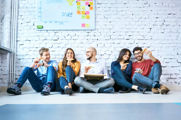 group of students sitting on floor at campus and eating pizza. young startup businesspeople during lunch break - eating technology stock pictures, royalty-free photos & images