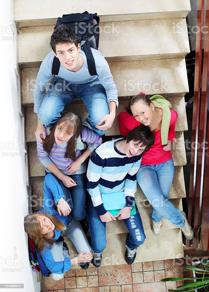 Grupa studentów, siedząc na schodach w szkole. – zdjęcie