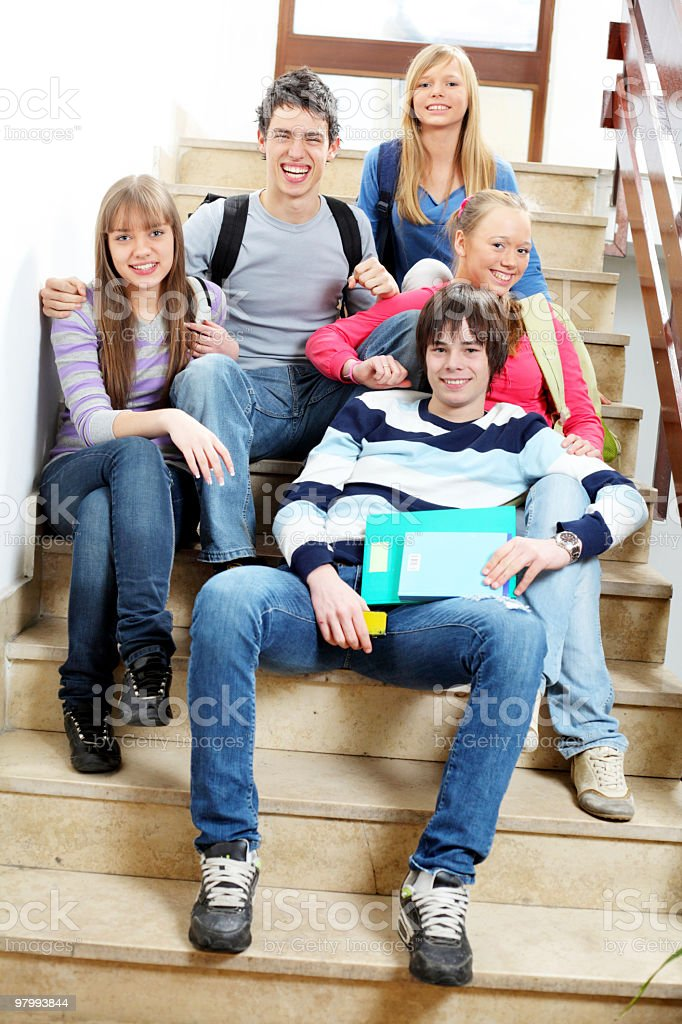 Group of students sitting on the stairs in a school. royalty free stockfoto