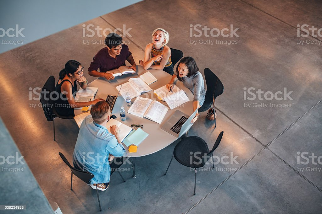 Group of students sitting together at table stock photo