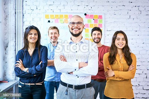 istock Group of students standing together in classroom and smiling. Portrait of startup entrepreneurs with arms crossed 1007730000