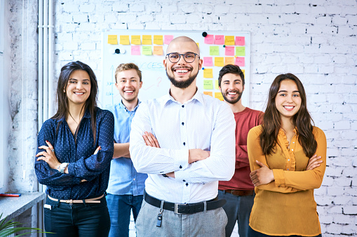 Group Of Students Standing Together In Classroom And Smiling Portrait Of Startup Entrepreneurs With Arms Crossed Stock Photo - Download Image Now