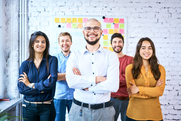 Group of students standing together in classroom and smiling. Portrait of startup entrepreneurs with arms crossed stock photo