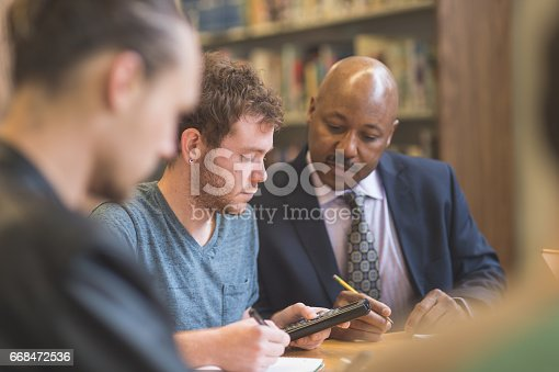 istock Group of students study diligently in university library while a professor helps them understand the difficult concepts 668472536