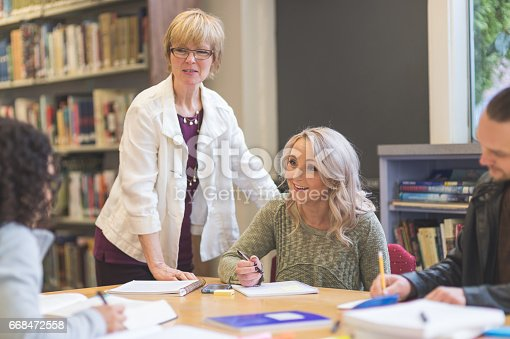 istock Group of students study diligently in university library while a professor helps them understand the difficult concepts 668472558