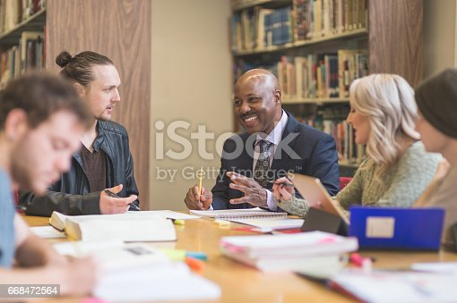 istock Group of students study diligently in university library while a professor helps them understand the difficult concepts 668472564