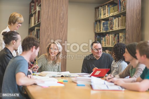istock Group of students study diligently in university library while a professor helps them understand the difficult concepts 680254478