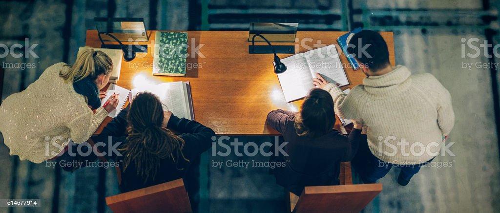 Grupo de estudiantes en una biblioteca estudiando - foto de stock