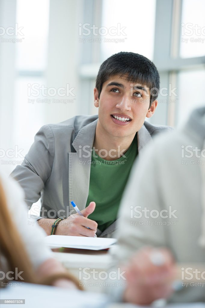 Group of students studying together in classroom. stock photo