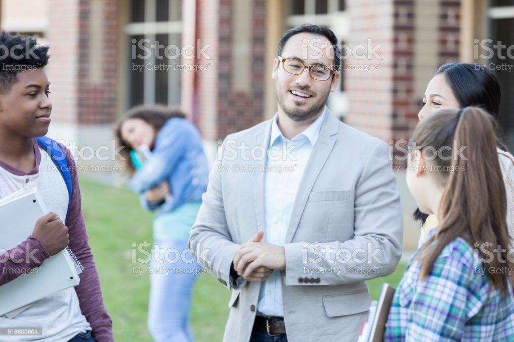 Confident high school teacher or principal talks with a group of high...