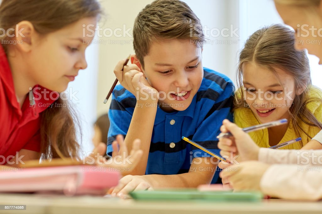 group of students talking and writing at school stock photo