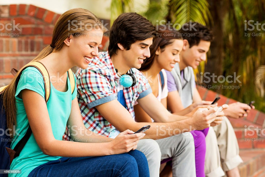Group Of Students Text Messaging On Smart Phone At Campus royalty-free stock photo