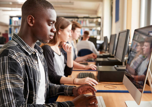 group of students using computers in college library - student stock photos and pictures