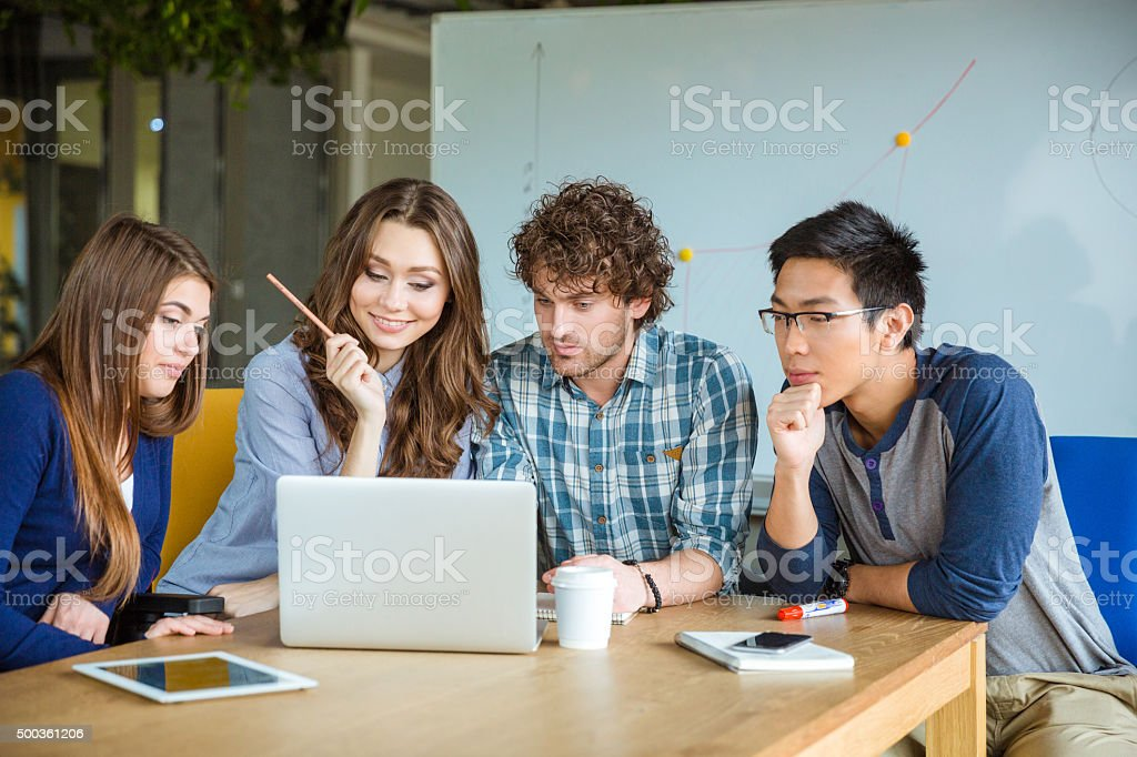 Group of students using laptop together stock photo