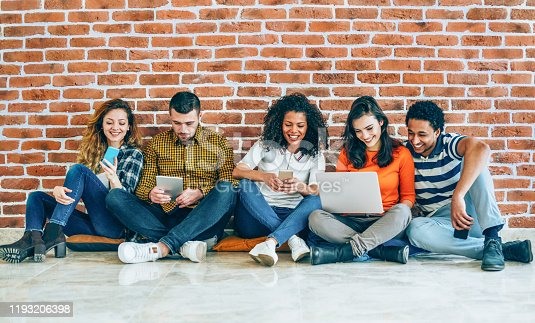 Group of young people with smart phones, digital tablets and laptop sitting in a row in front of brick wall