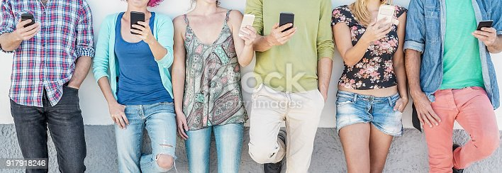 istock Group of students using smartphones while watching videos outdoor - Teenagers friends having fun with technology trends - Youth, tech and friendship concept 917918246